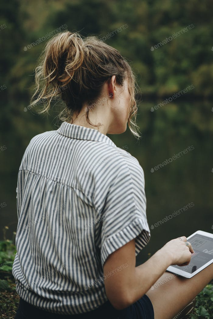 A woman alone in nature using a digital tablet