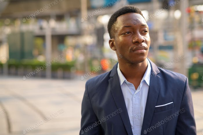 Face of young handsome African businessman thinking in the city