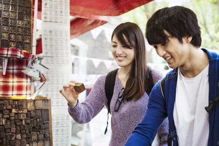 A young Japanese couple at a souvenir street stall looking at printing blocks for sale.