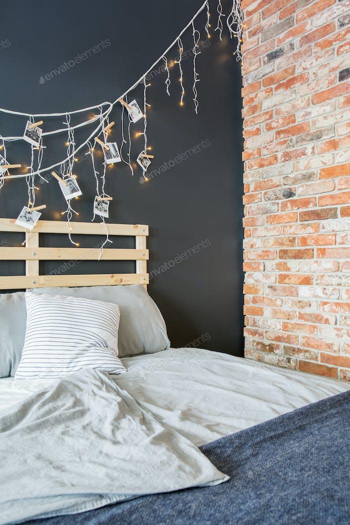 Bed next to brick wall