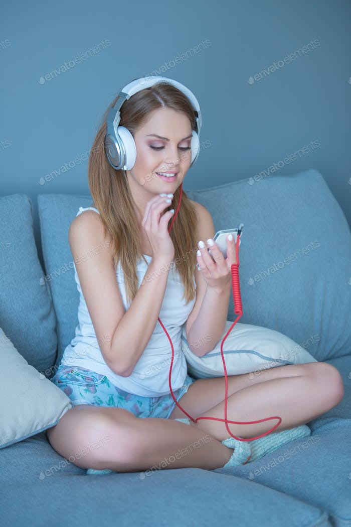 Young woman selecting music on her MP3 player