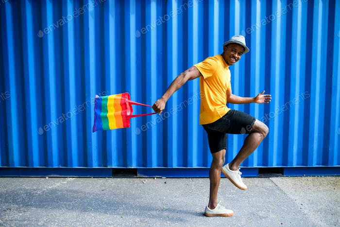 Young black man with rainbow bag walking, black lives matter concept