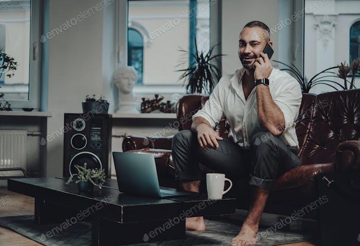 Joyful businessman sitting at sofa talks on smartphone in apartment