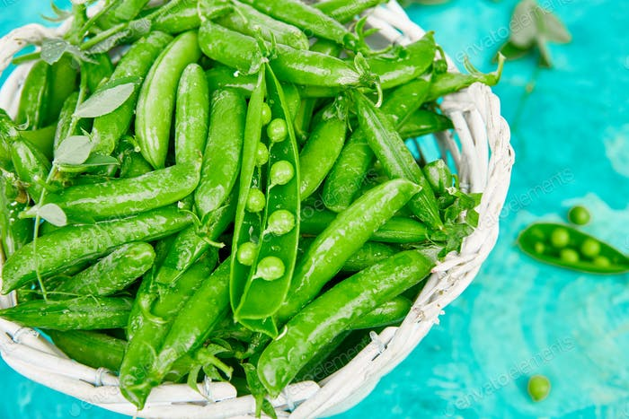 White Basket with fresh green peas on blue background.