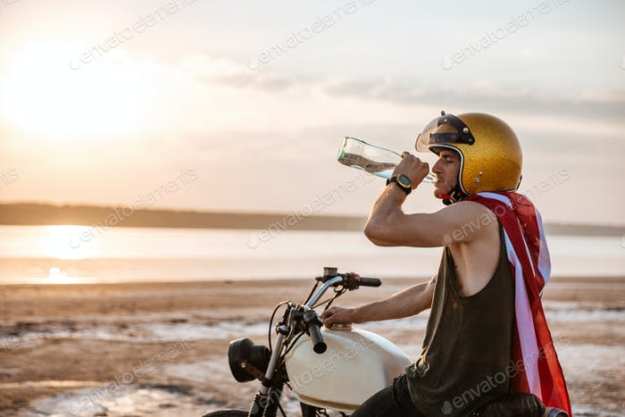 Man in drinking while sitting on his motocycle