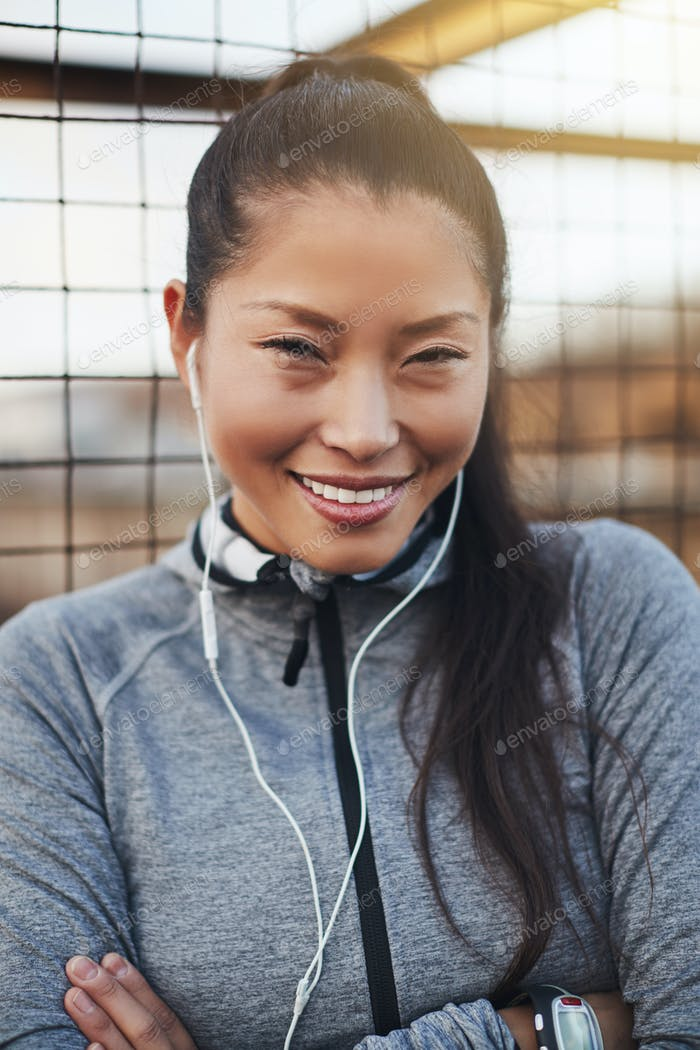 Fit young Asian woman in sportswear smiling before a jog