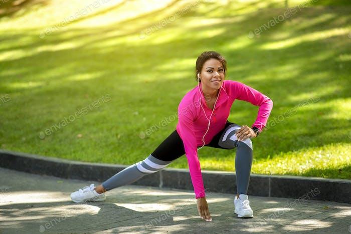 Motivated black woman exercising at public park