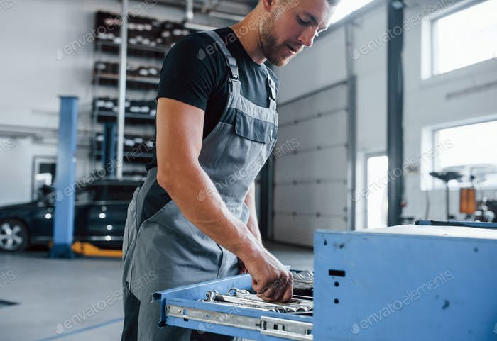 Different sizes. Male mechanic use different tools to repair broken automobile in garage