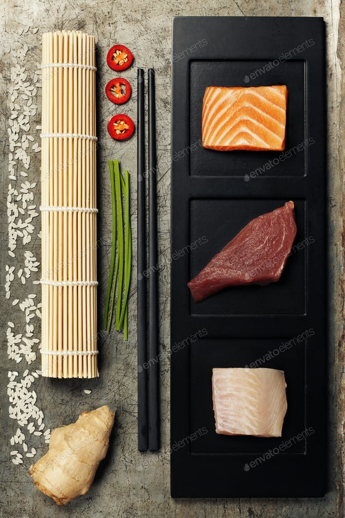 assortment of raw fish and ingredients for making sushi