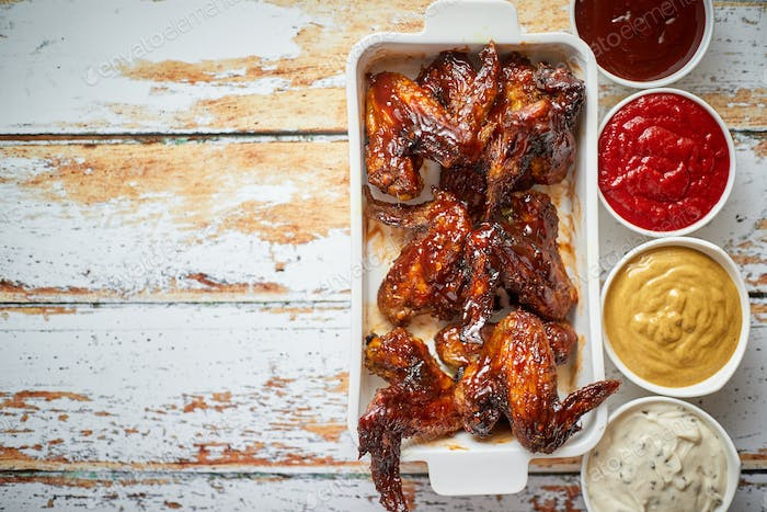 Chicken wings in thick barbecue sauce with various side dips. Served on white cast iron dish