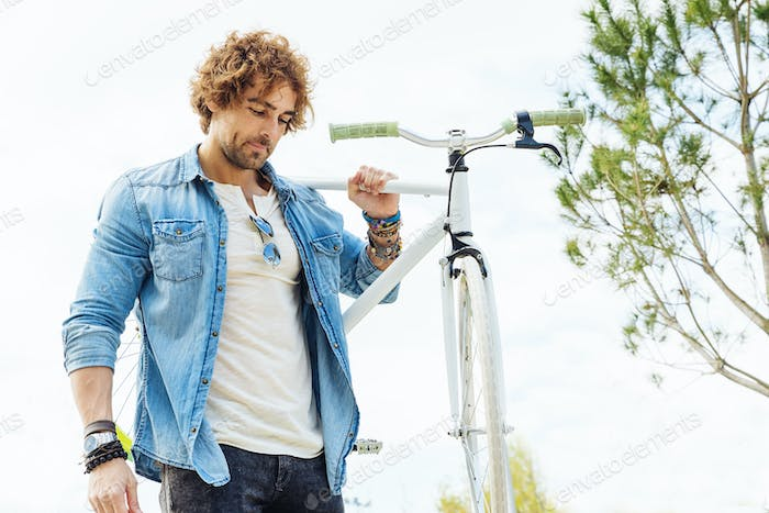 Handsome young man with fixed gear bicycle in the street.