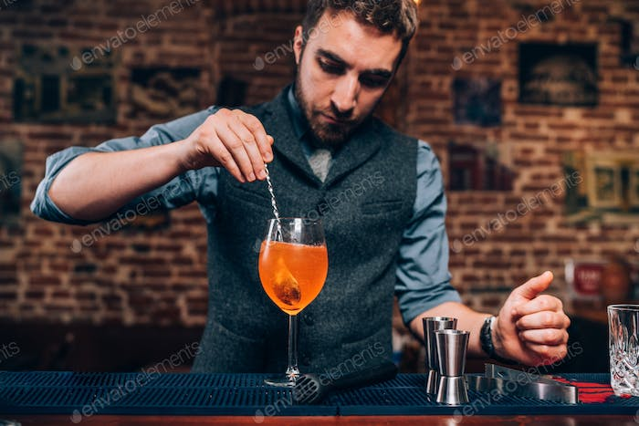 Portrait of professional bartender preparing cocktail, refreshing alcoholic drink in nightclub