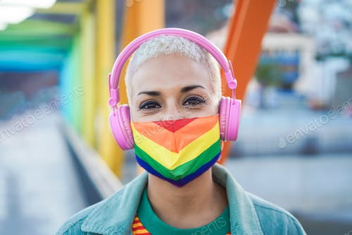 Young lesbian listening music with headphones while wearing rainbow flag mask - Focus on face