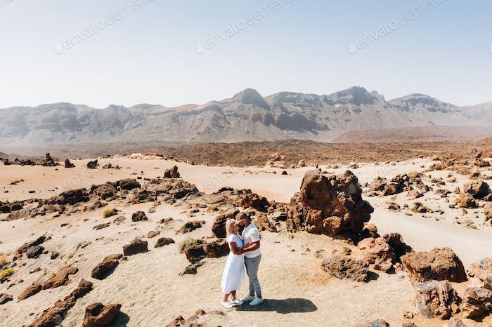 People in love kiss in the crater of the Teide volcano. Desert landscape in Tenerife. Teide National