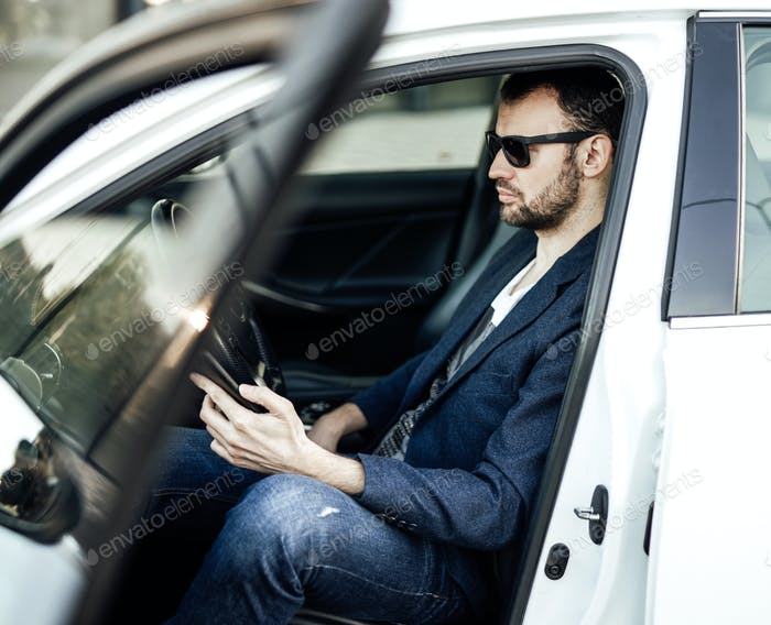 Fashion rich man looking at phone and sitting in the car