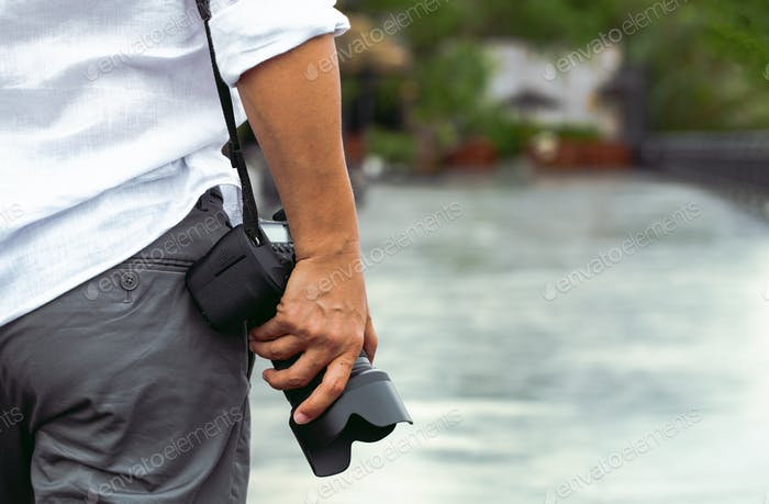 Man with photo camera Fashion Travel Lifestyle outdoor nature on sun light background