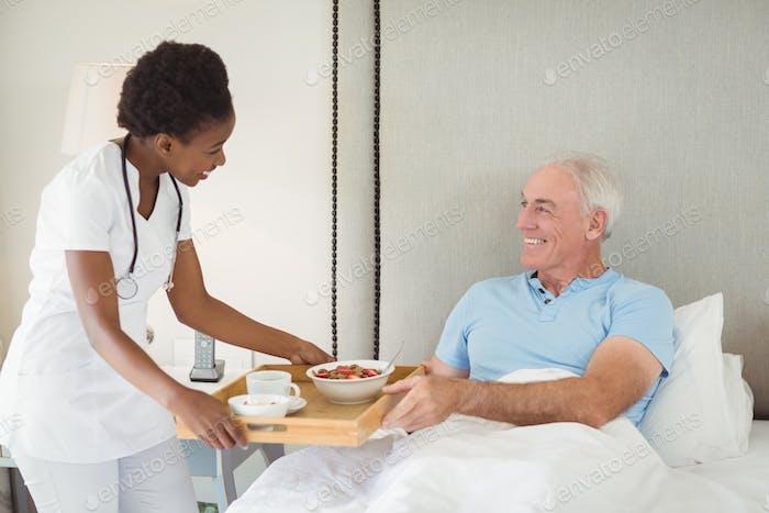 Krankenschwester serviert Frühstück für ältere Patienten