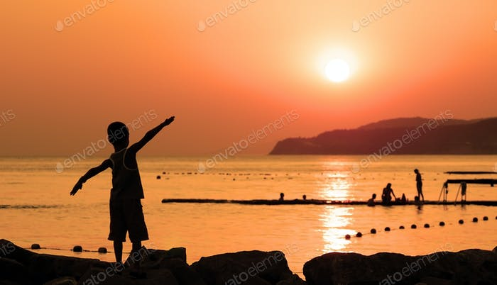 Silhouette of child against orange sunset at sea with spread his hands