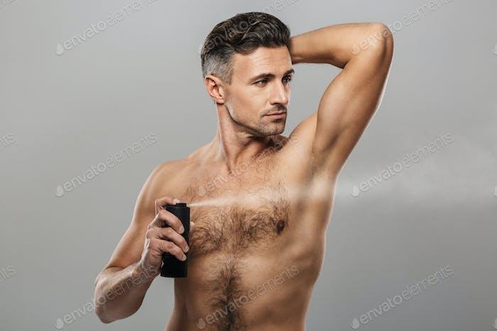 Mature man standing holding deodorant.