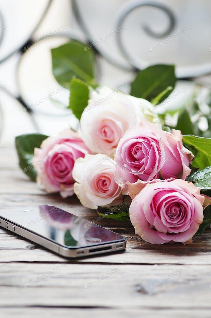 Rosa Rosen und Smartphone auf dem Holztisch