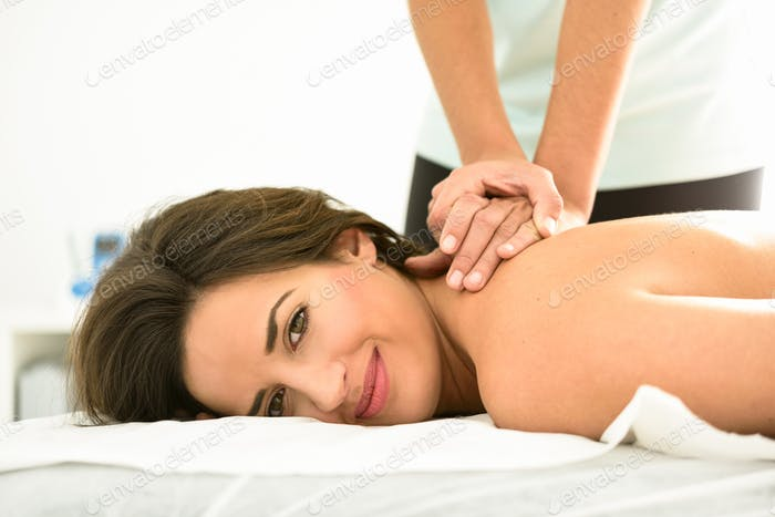 Young woman receiving a back massage in a spa center.