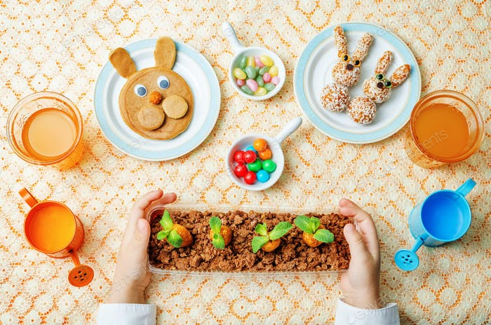 children's hands with pancakes, sweets and juice for Easter