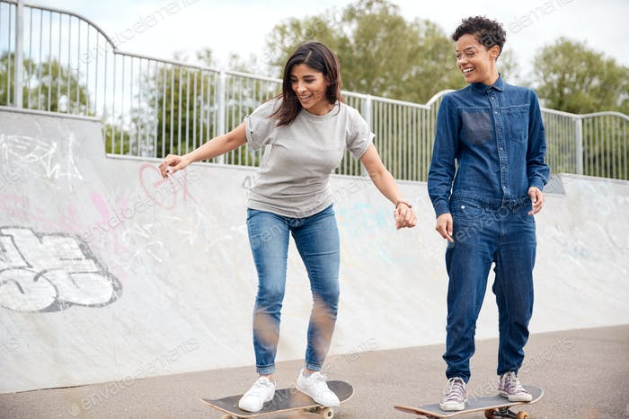 Two Female Friends Riding On Skateboards In Urban Skate Park