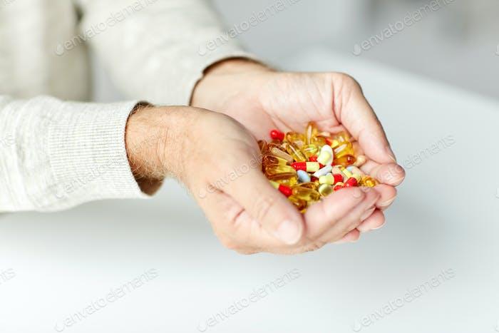 close up of senior man hands holding pills