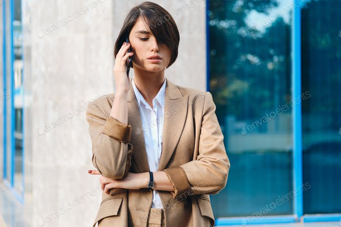 Young confident stylish businesswoman in suit talking on cellphone outdoor
