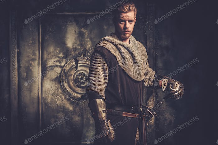 Young medieval knight standing on dark background.