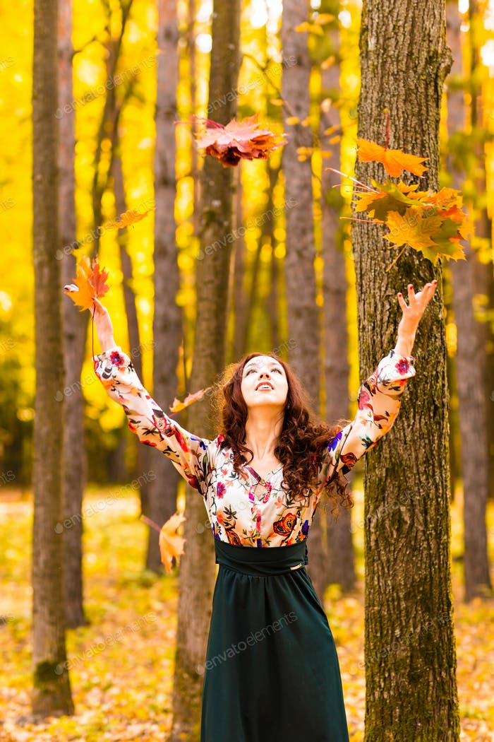 Young beautiful woman throwing  yellow leafs in the air