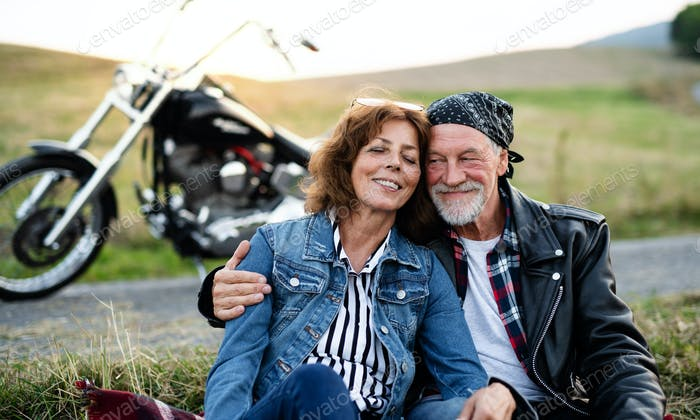 A senior couple travellers with motorbike in countryside, resting.