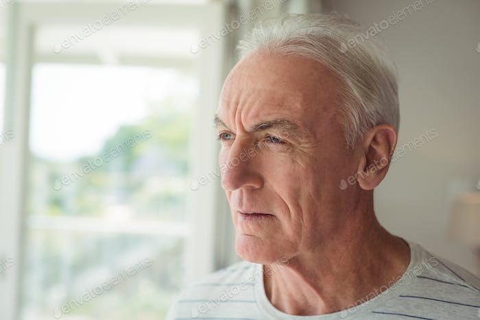 Thoughtful senior man standing next to window