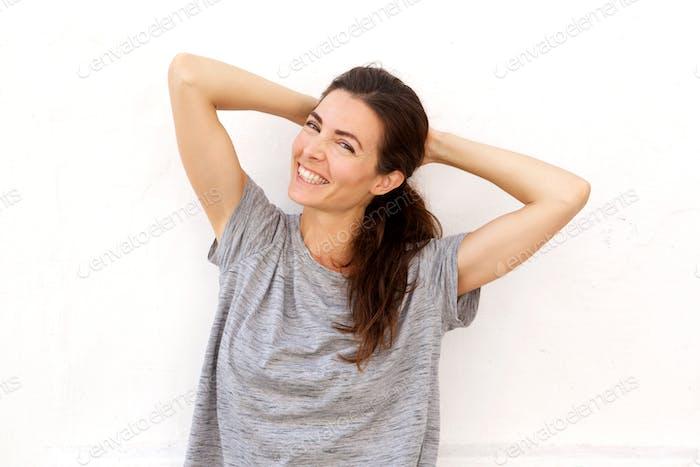 attraktive junge Frau mit ihren Händen hinter dem Kopf und lächelnd gegen weiße Wand