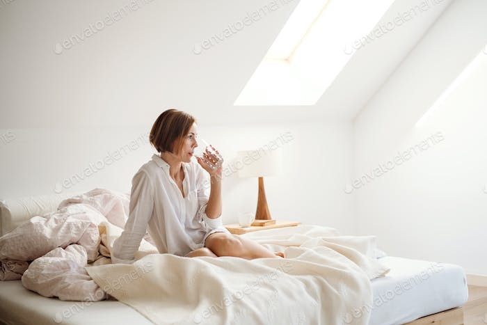 A young woman with night shirt sitting indoors on bed in the morning, drinking water.