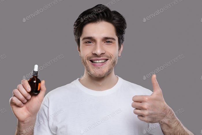 Handsome man approving face serum, showing thumb up gesture