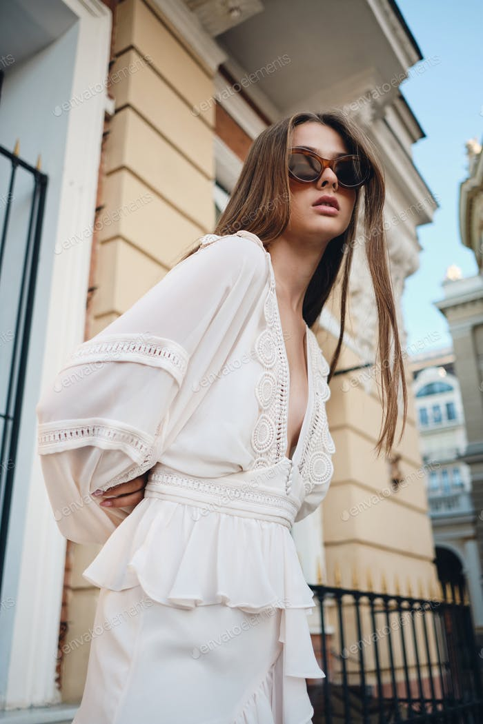 Young attractive girl in sunglasses and white dress looking in camera posing on cozy city street