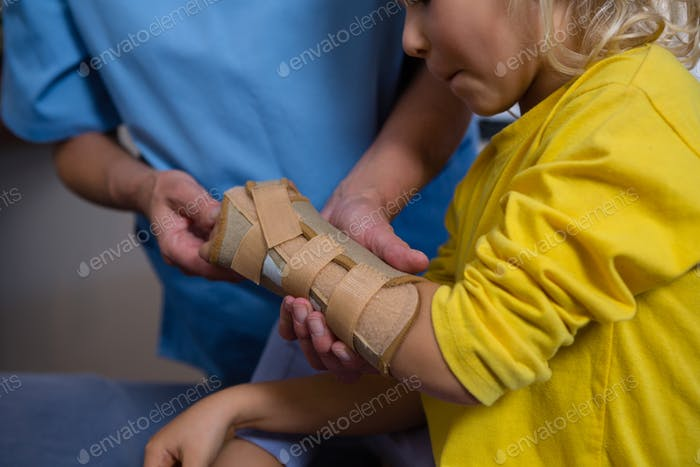 Female physiotherapist giving hand massage to girl patient