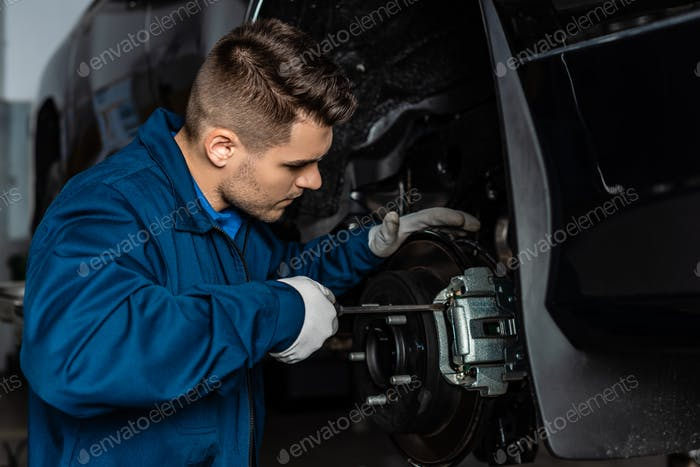 attentive mechanic adjusting brake caliper with screw driver