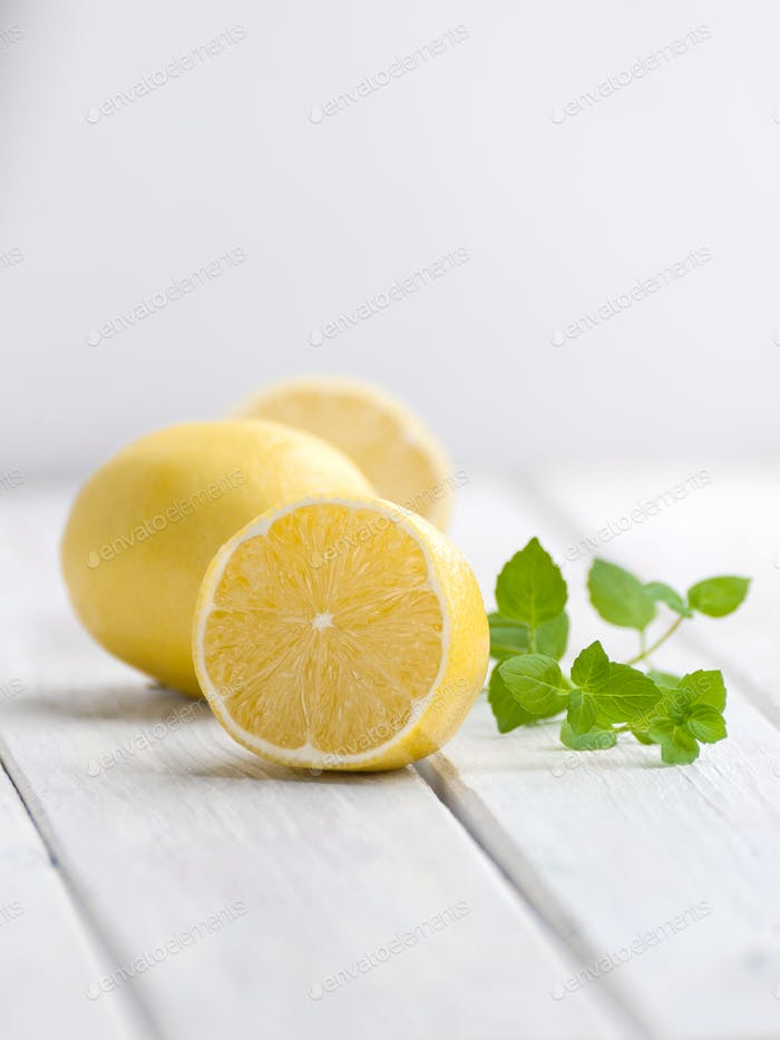 Half a ripe lemon and a mint branch on a white wooden table.