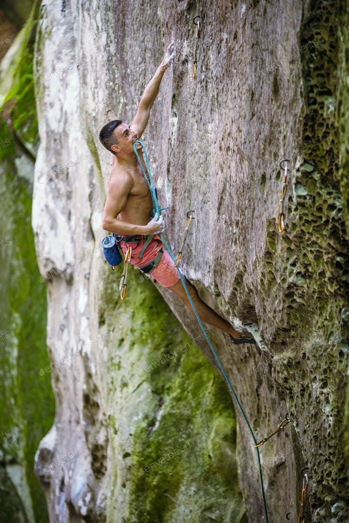 Rock climber holding rope with teeth before making clip
