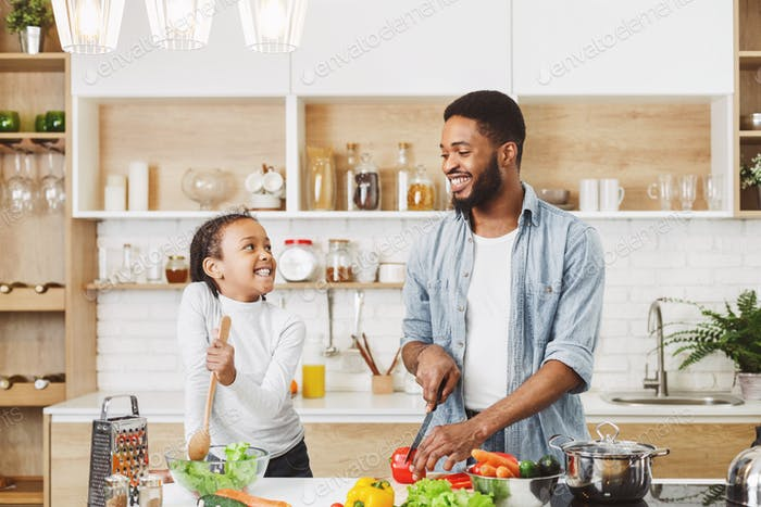 African father and daughter having fun while cooking veggies