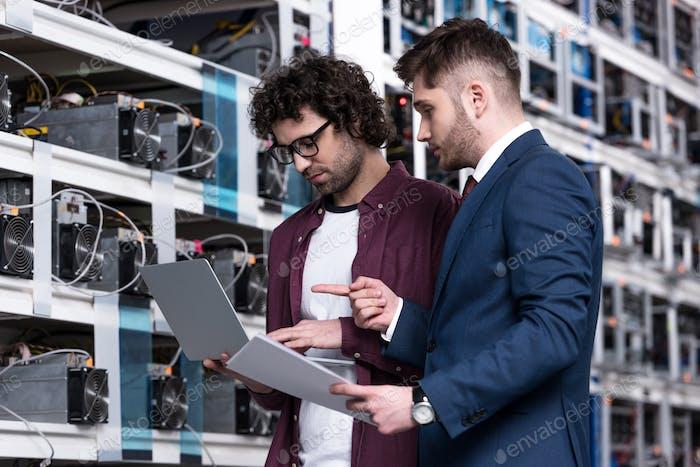 empresario e ingeniero informático trabajando con el ordenador portátil juntos en la granja minera de bitcoin