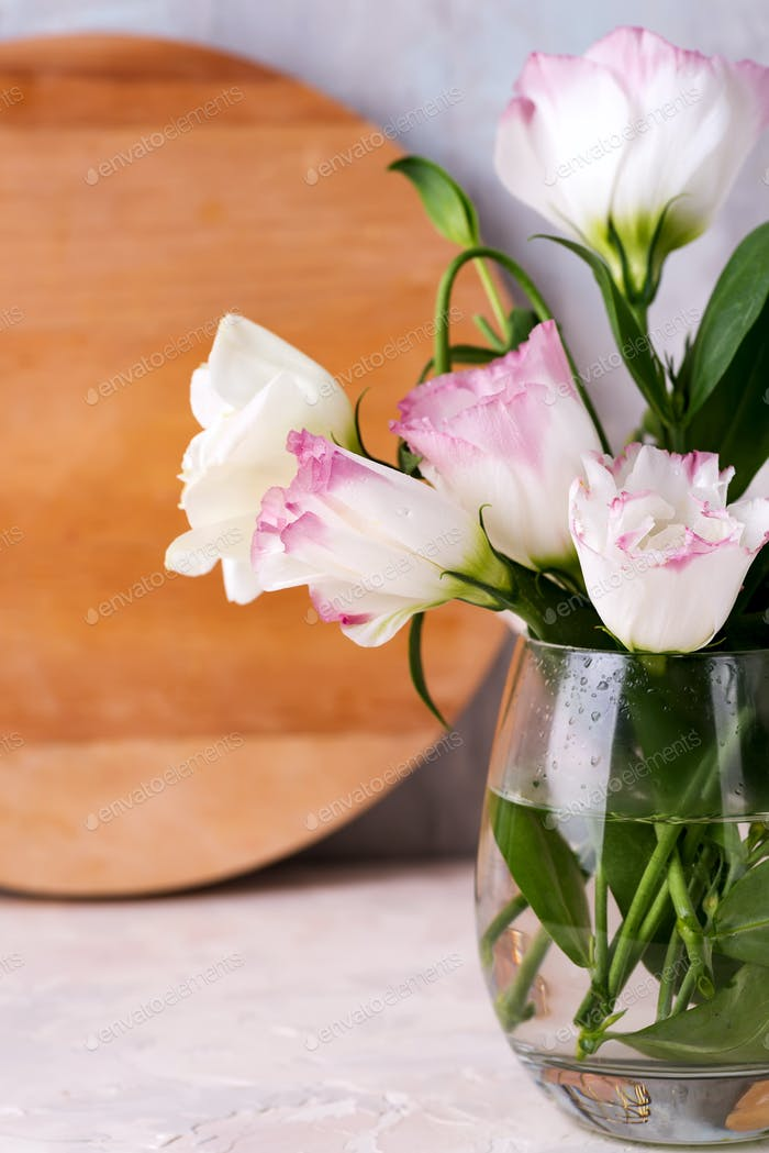 Eustoma flowers in vase on table near wooden plate and stone wall, close-up. Blank for postcards