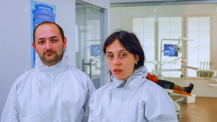 Portrait of team doctor in dental office taking off protective masks