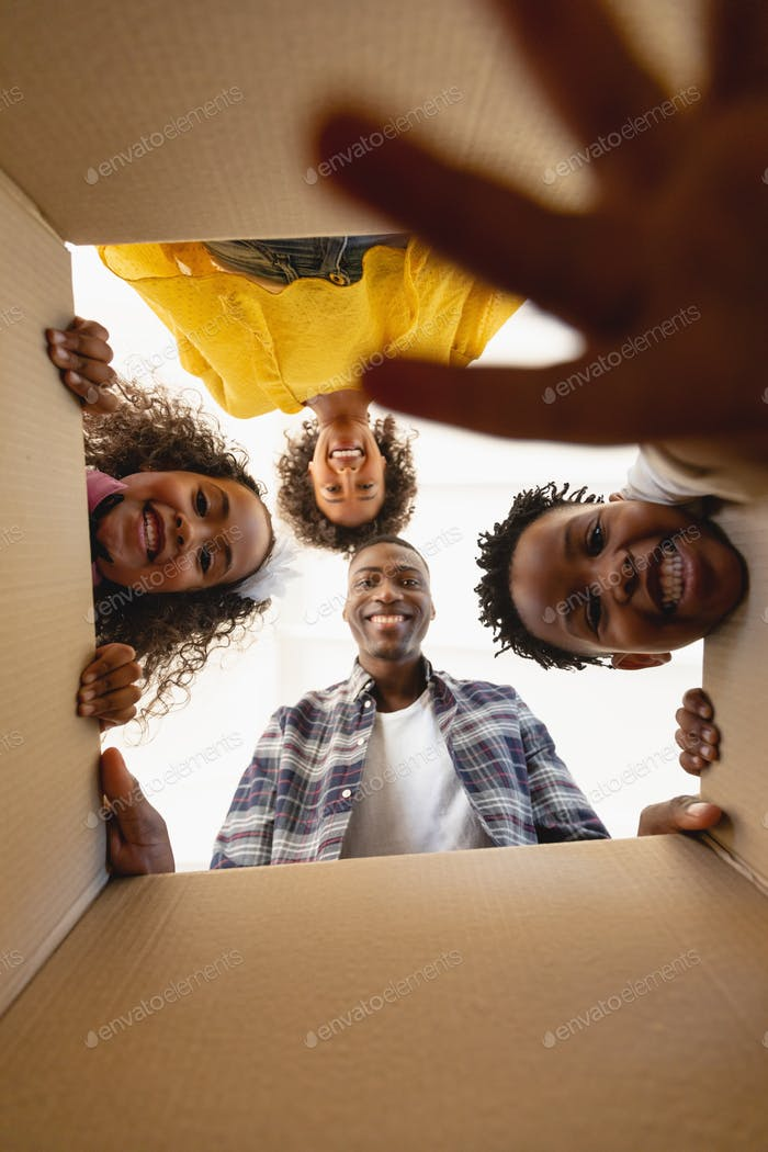 Upward view of happy African American family unpacking their belongings at home