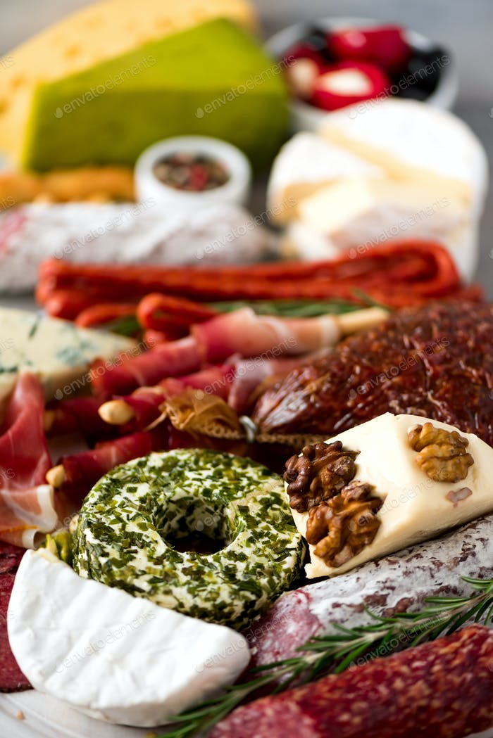 Traditional italian antipasto, cutting board with salami, cold smoked meat, prosciutto, ham, cheeses