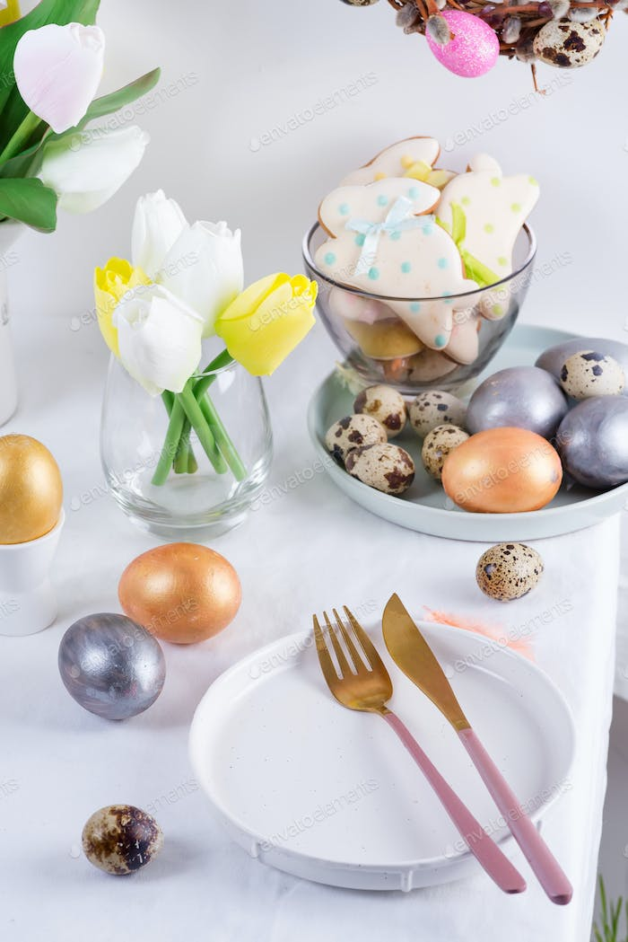 Holiday Easter table setting with craft painted eggs, baked cookies and fresh flowers on a table