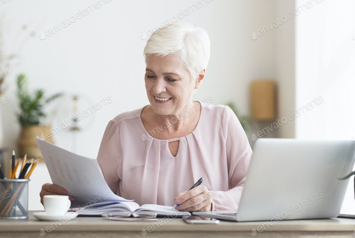 Mature editor reading printed text and making notes