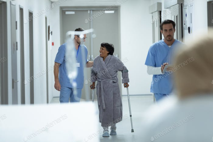 Caucasian male doctor interacting with disabled female patient in the corridor at hospital